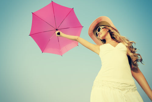 Woman in white dress and hat holding pink umbrella in the air.