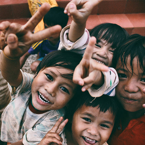 Several young children smiling together at the camera and making the peace symbol with their hands.