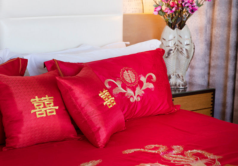 A bed set up with red double happiness pillows and bed spread