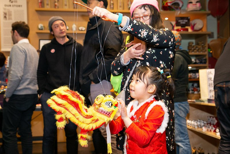 Little girl and her mother playing with a Chinese lion puppet