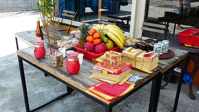 Offerings of incense, paper money, and fruit for hungry ghosts