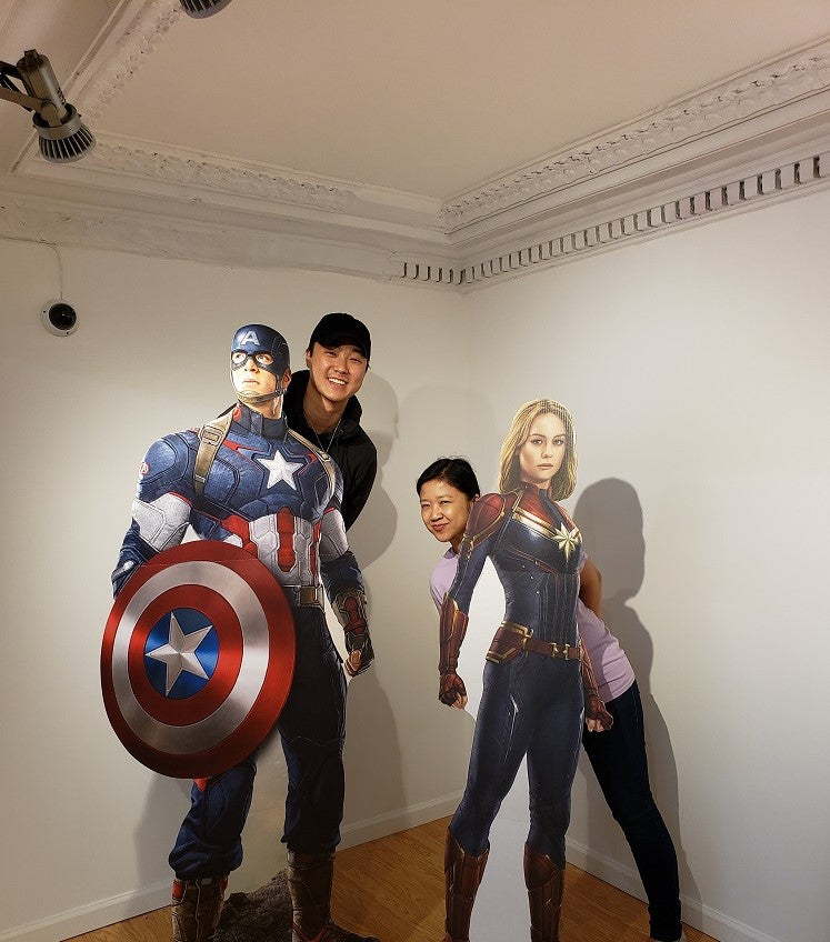 The artist William Yu and Pearl River President Joanne Kwong posing with cardboard cutouts of Captains America and Marvel