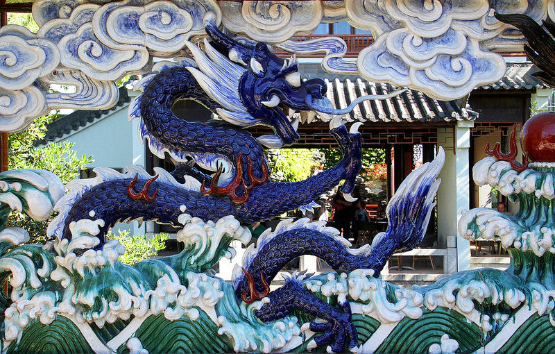 Mosaic of blue dragon in clouds and above water