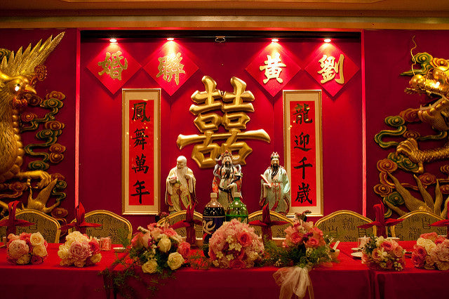 A large gold double happiness wall hanging with auspicious scrolls behind a table set with red tablecloth and flowers for bride, groom, and wedding party
