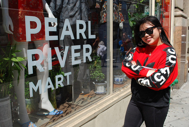 College student Tiffany with sunglasses in front of Pearl River Mart store