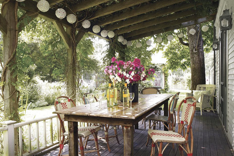 Beautiful porch with table, chairs, vase with flowers, and string of white Pearl River lanterns