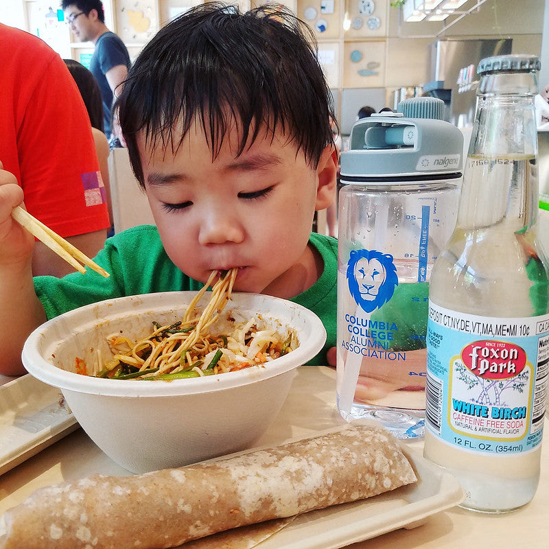 A boy enjoys a bowl of noodles