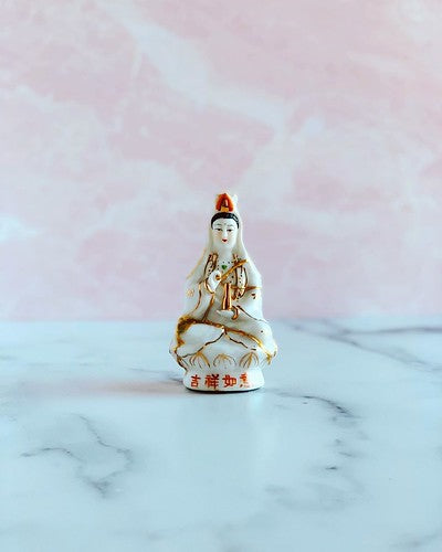 Peaceful white figurine of Guan Yin against a bright background
