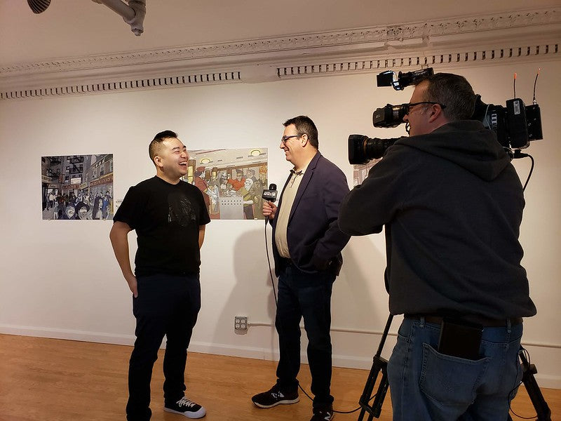 Artist Jerry Ma speaks with NY1 reporter Roger Clark in Pearl River's art gallery