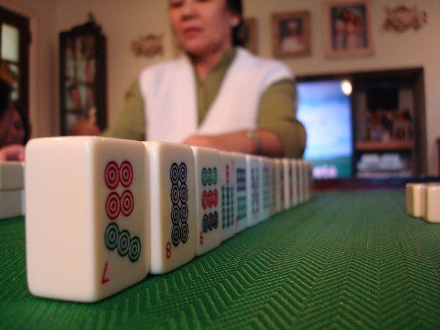 A row of mahjongg tiles on a green table with a lady in the background