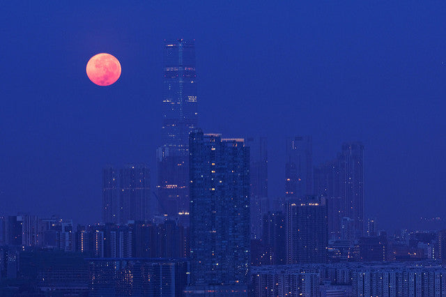 A night view of a city with a beautiful pink moon