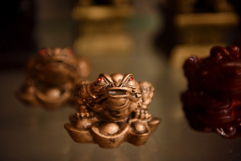 A gold colored money toad figurine with red eyes