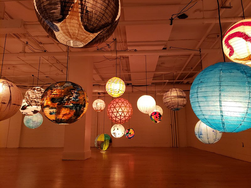 Individually painted lanterns hanging in a gallery
