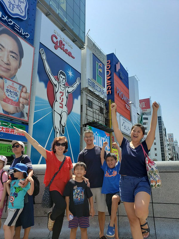 Joanne Kwong and her family in front of the Glico running man billboard in Osaka