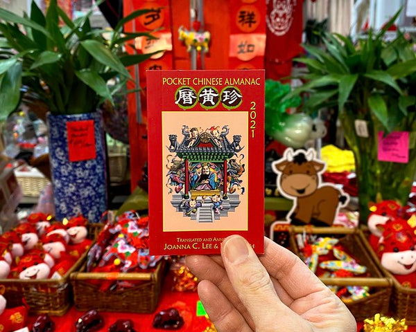 Chinese pocket almanac held in front of Lunar New Year display