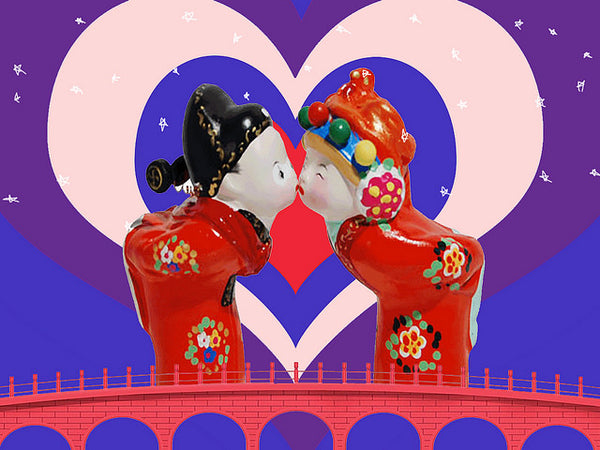 Two Chinese dolls sharing a cute kiss on a bridge