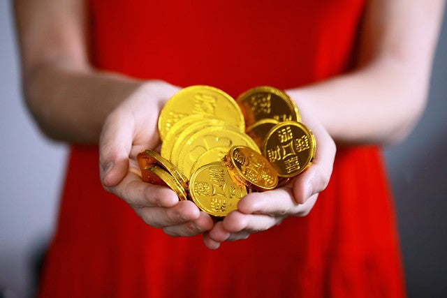 Woman in red dress holding gold chocolate coins