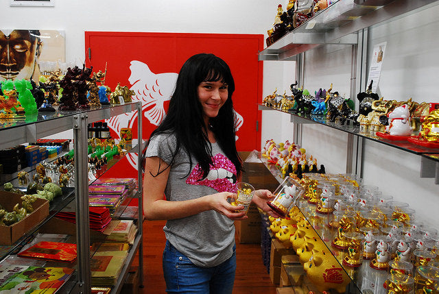 College student Skye in Pearl River Mart, browsing lucky cat figurines