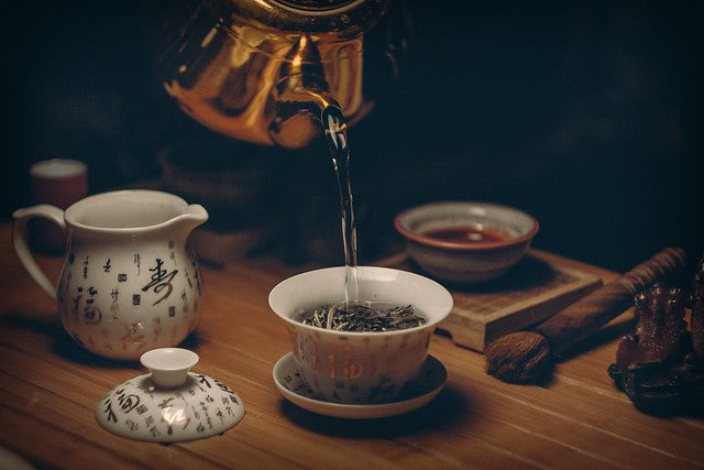 Chinese tea cups with kettle pouring water over tea leaves