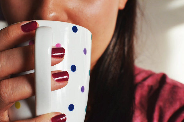 Woman drinking mug of hot tea