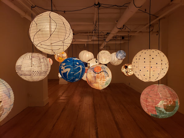 Another selection of individually painted lanterns hanging in a gallery