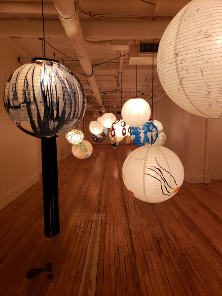 More individually painted lanterns hanging in a gallery