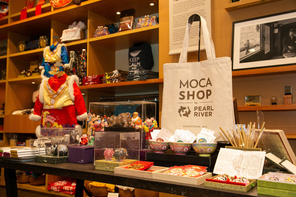 MOCA Shop by Pearl River tote bag on a table with other items