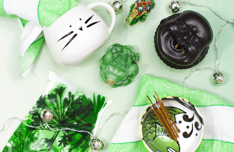 Arrangement of Ruby's purchases, including white cat mug, green and white sauce dish, green frog, Buddha head incense holder, and more