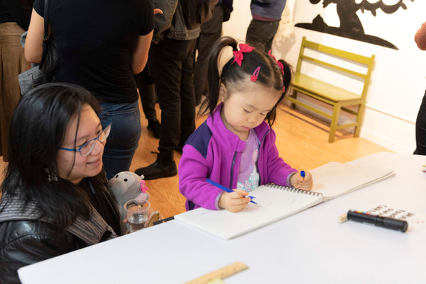 Little girl drawing during Asian Babies art exhibition