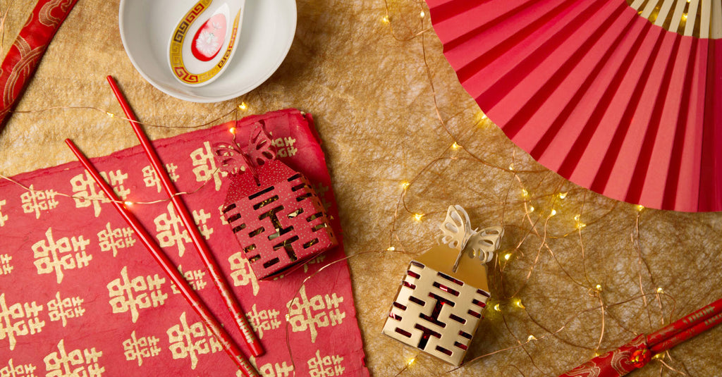 Beautiful arrangement of double happiness wrapping paper, chopsticks, candy boxes, fan, and bowl with spoon
