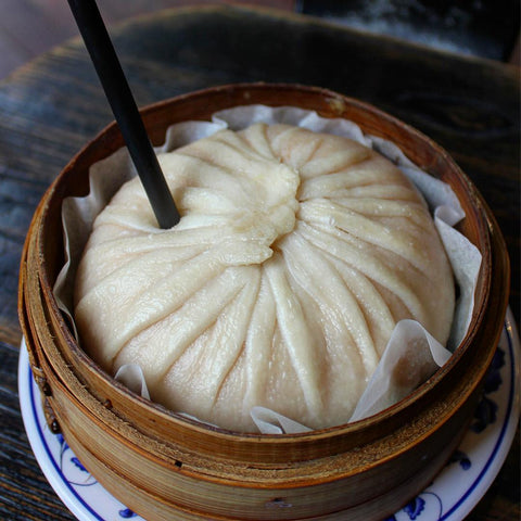 A very large soup dumpling in a steamer with a straw