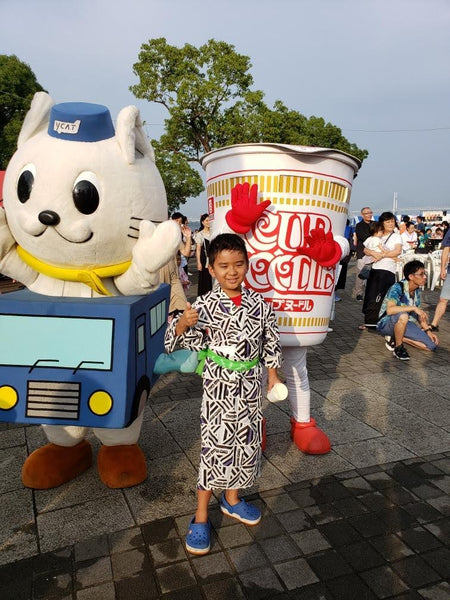 Child in traditional yukata giving a thumbs up in front of a Cup Noodles mascot