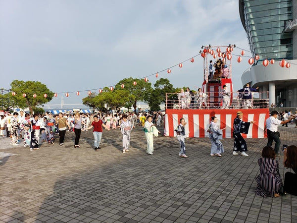 Line of festive bon odori dancers in traditional Japanese clothing at a bon festival