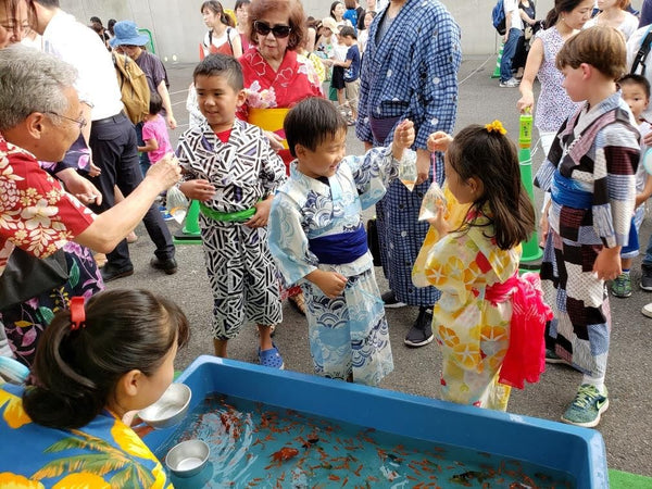 Children in traditional yukata playing games at a bon festival