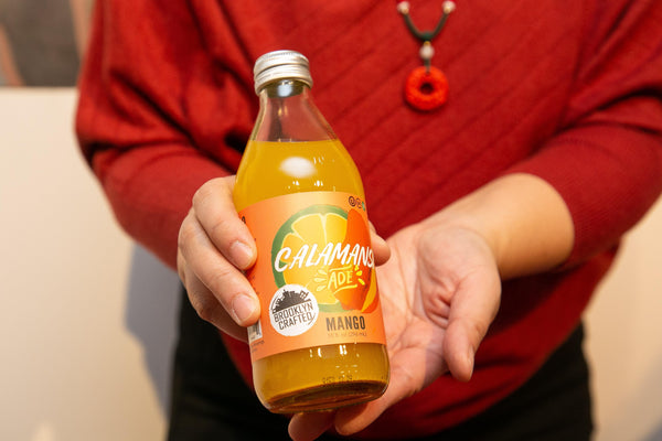 Person holding bottle of Brooklyn Crafted mango calamansi aid