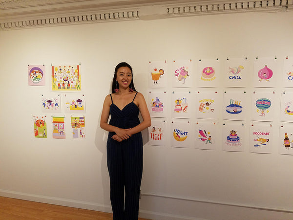 Illustrator Dingding Hu in front of her work