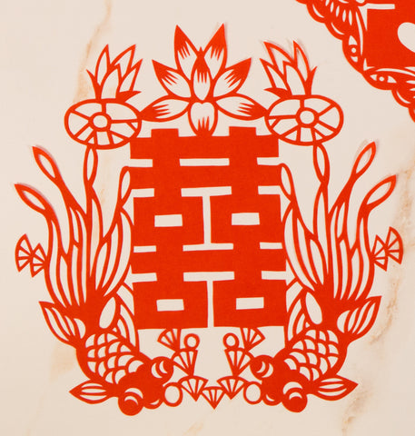 Red papercut decoration of double happiness symbol with two fish
