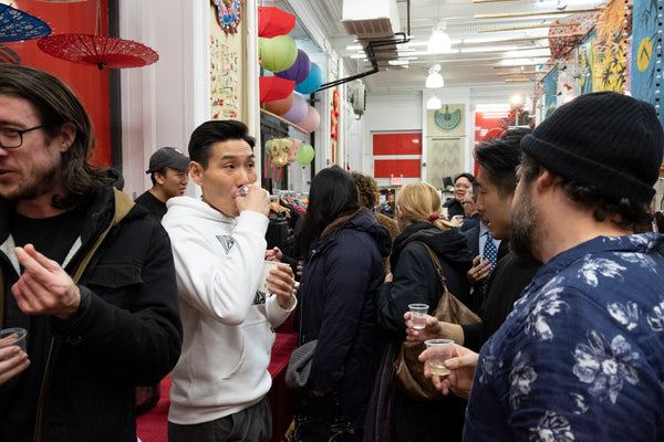 Guests enjoying drinks at Jerry Ma's opening reception for his art show at Pearl River Mart