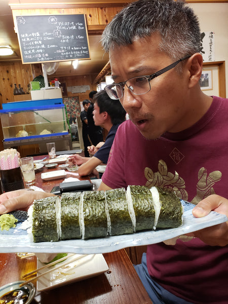 A man astonished a very large sushi roll
