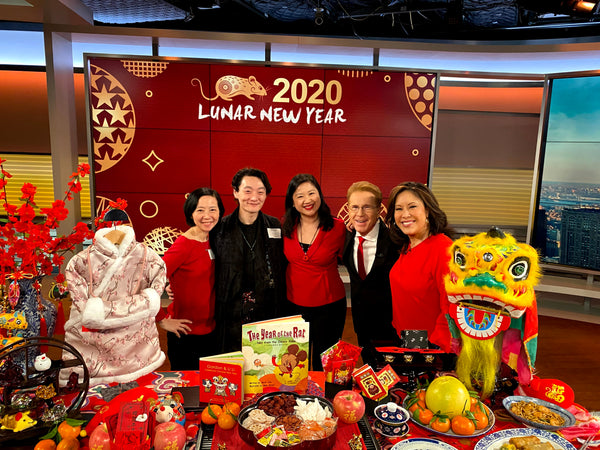 Joanne Kwong and Pearl River staff with CBS's Cindy Hsu and John Elliott in front of display of Lunar New Year decor and foods