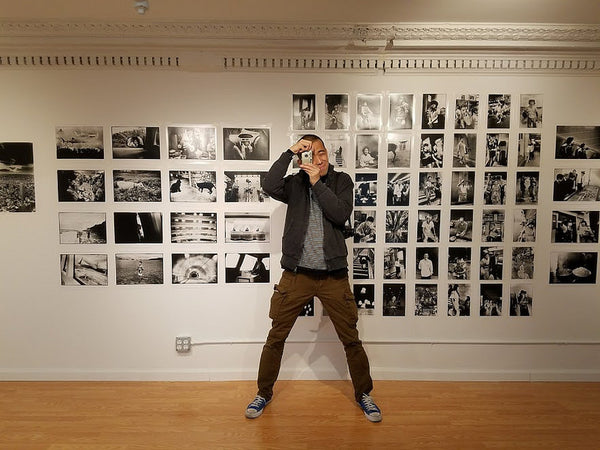 Photographer Hiro Ito posing in front of his photographs