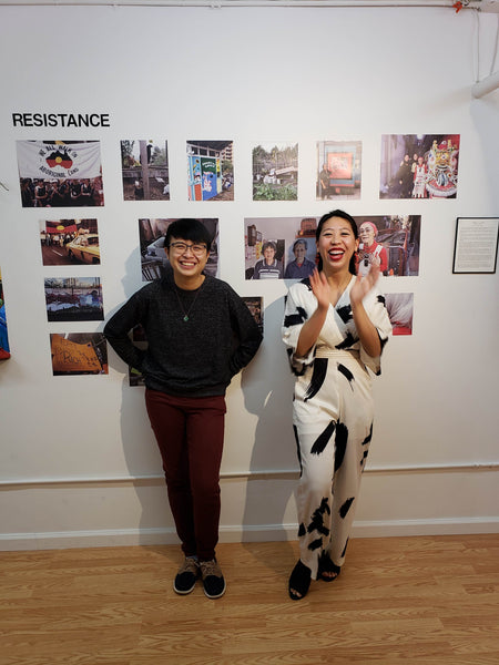 Former artists-in-residence Huiying B. Chan and Diane Wong in front of their photographs of different Chinatowns around the world