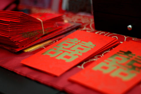 Stacks of hong bao, or red envelopes, with double happiness characters