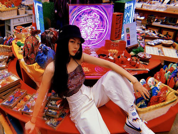 Artist Juno Shen posing in front of one of her neon light mahjong tile sculptures