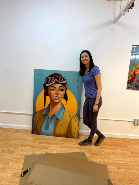 Curator Kelly Lan with portrait of Hazel Lee, early Chinese American female fighter pilot