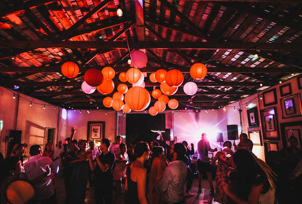 Guests dance under colorful lanterns