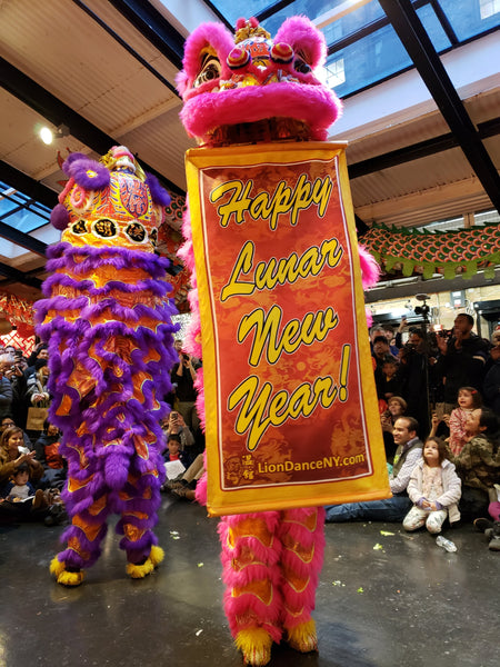 Lion dancers holding Lunar New Year sign