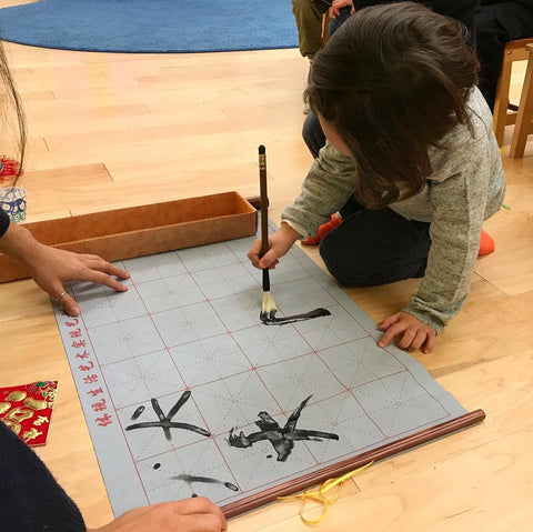 Child practicing Chinese calligraphy with a reusable set