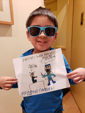 Kid with sunglasses holding drawing