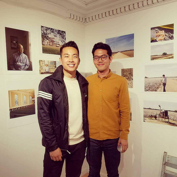 Photographers Andrew Kung and Emanuel Hahn posing in front of their photos